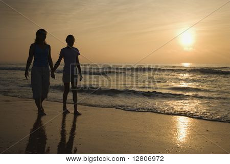 Caucasian prime adult female and female child walking on beach at sunset holding hands.