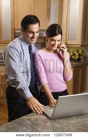 MId-adult female talking on phone and mid-adult male both looking at laptop computer in kitchen.
