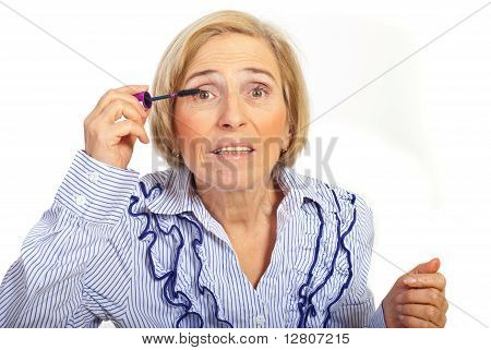 Senior Woman Apply Mascara On Eyes