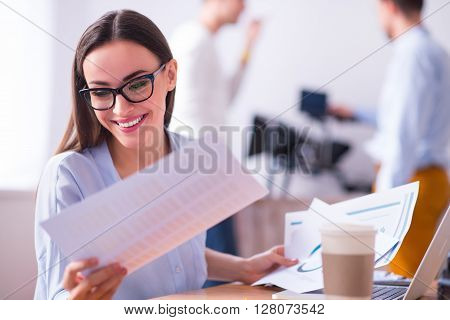 Have a good mood. Cheerful beautiful delighted smiling woman sitting at the table and working with papers while her colleagues standing in the background