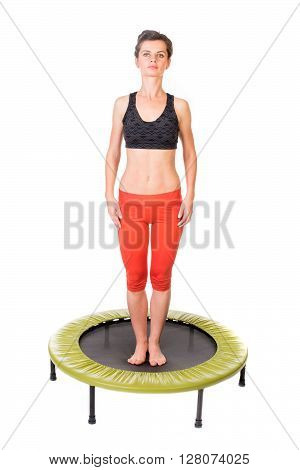 Closeup of a fit young woman standing on a fitness trampoline - isolated on white.