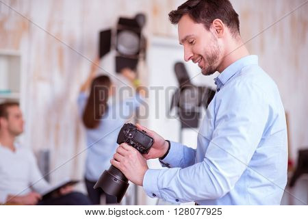 Like my occupation. Pleasant smiling delighted handsome man holding photo camera and working in photo studio while expressing gladness