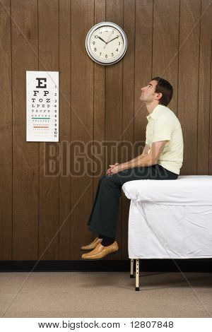 Caucasian mid-adult male waiting on table in retro doctor's office.
