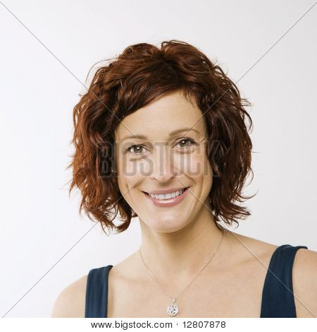 Portrait of Caucasion mid-adult attractive woman looking at viewer and smiling.