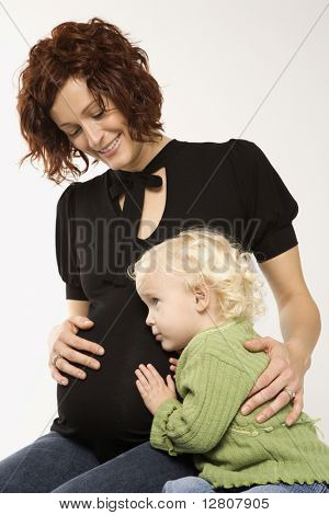 Young Caucasian female child with ear against her mother's pregnant belly.