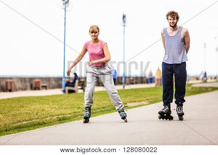 Outdoors activities sport and free time. Summertime exercising and healthy body. Young couple have fun together rollerblading in park.