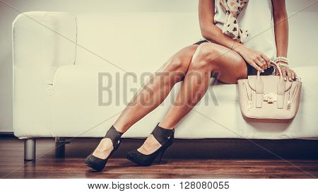 Elegant outfit. Female fashion. Girl in fashionable clothes sitting on sofa holding bag handbag.