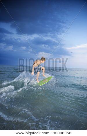 Caucasian male teen riding skimboard.