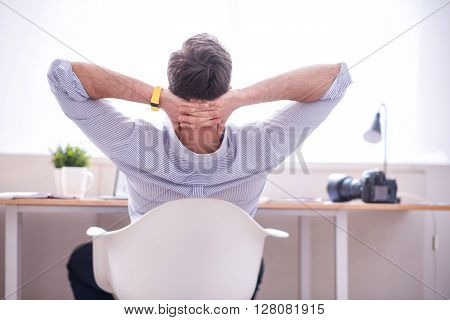 I deserve some rest.  Pleasant relaxed man sitting in the chair at the table and holding his hands behind the head while being turned back