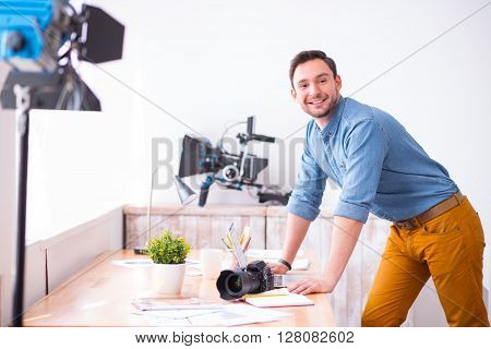 Enjoy every day. Pleasant delighted handsome smiling man leaning on the table and expressing gladness while working in photo studio