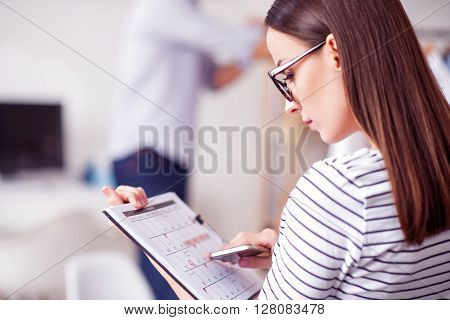 Keep the pace of time. Pleasant beautiful concentrated woman holding calendar and cell phone while being involved in work