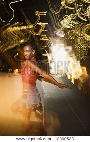 Young sexy African-American woman on patio in New York City, New York at night with blurred lights.