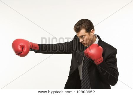 Caucasian mid-adult man wearing suit and punching with boxing gloves.
