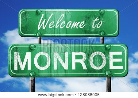 monroe vintage green road sign with blue sky background