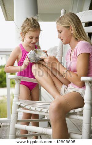 Niña preadolescente caucásica mostrando la concha a otra niña caucásica.