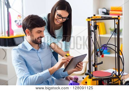Joyful mood. Cheerful delighted smiling colleagues using tablet and expressing joy while 3d printer working on the table