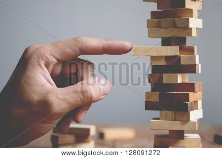 Planning risk and strategy in business businessman and engineer gambling placing wooden block on a tower.