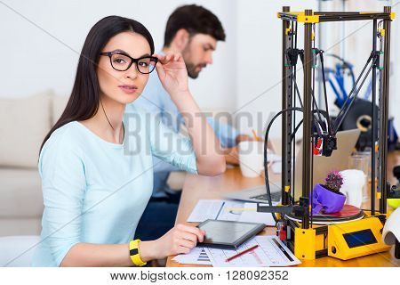 Concentrate on your goals.  Pleasant beautiful seducing girl sitting at the table and working with 3d printer while her colleague making notes in the background