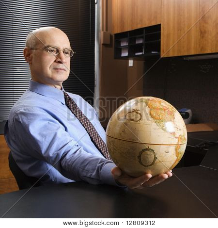 Caucasian middle-aged businessman sitting at desk in office holding globe.
