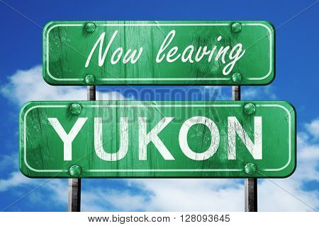 Leaving yukon, green vintage road sign with rough lettering