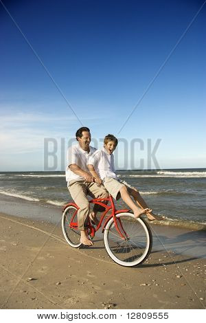 Caucasian father on bicycle with pre-teen boy riding on handlebars.