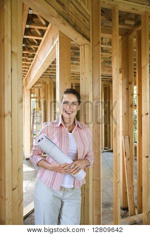Caucasian mid-adult female holding blueprints in building construction site.