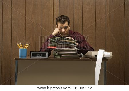 Caucasion mid-adult retro businessman with bored expression sitting at desk piled high with folders.