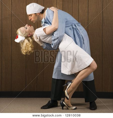 Mid-adult Caucasian male surgeon bending female nurse over backwards for passionate embrace.