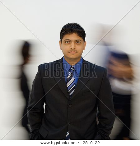 Indian businessman standing with hands in pockets while others walk by.