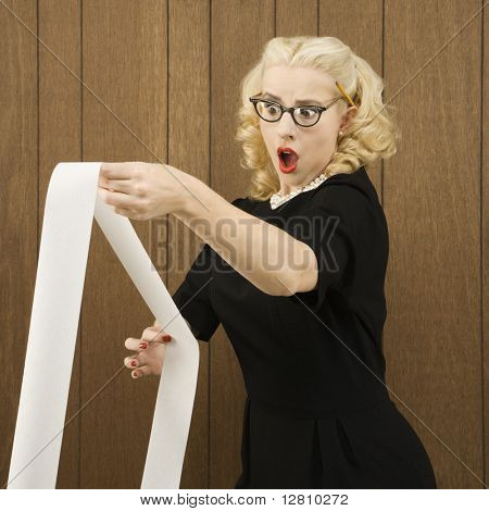 Mid-adult Caucasian female in vintage outfit holding a printout with a shocking expression on her face.