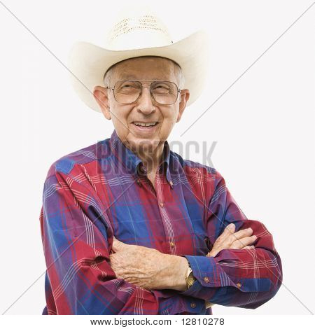 Portrait of smiling Caucasion elderly man wearing plaid shirt and cowboy hat with arms crossed.