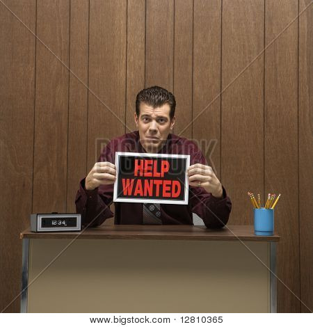 Caucasion mid-adult retro businessman with desperate expression sitting at desk holding up help wanted sign .