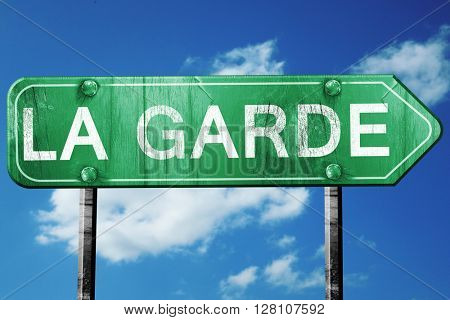 la garde road sign, vintage green with clouds background