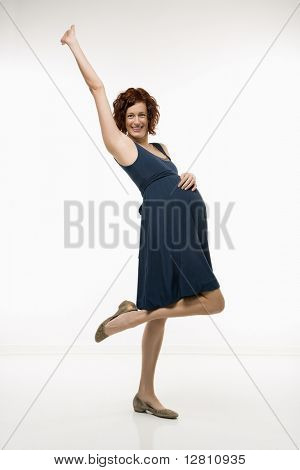 Portrait of Caucasion mid-adult attractive pregnant woman standing with one knee up, one hand on belly and other arm in air looking at viewer and smiling.