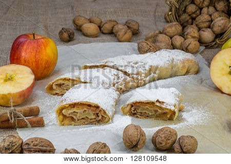 Sugared Homemade Apple Strudel on Baking Paper with Walnuts Cinnamon and Apple