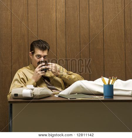 Caucasion mid-adult retro businessman sitting with feet propped on desk drinking coffee.