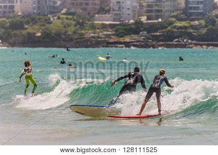 Manly Australia - November 9 2014: All ages surfers and paddle boarders surfing the wave on the Manly beach Sydney Australia.
