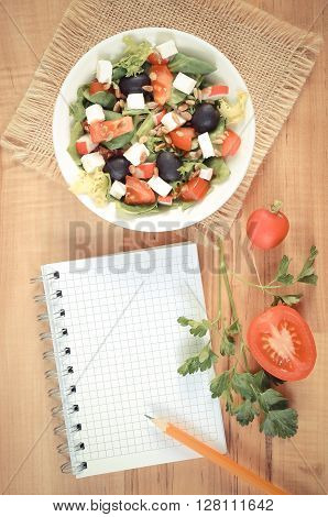 Vintage photo Fresh greek salad with vegetables and notepad for writing notes concept of healthy nutrition lifestyle and slimming