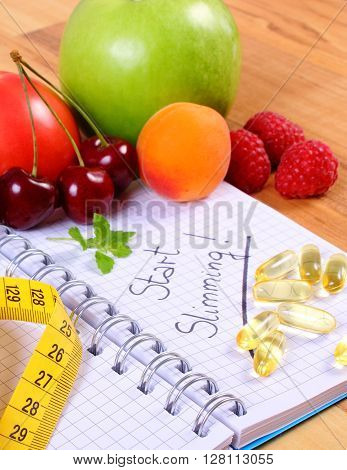 Fresh fruits vegetables tape measure and tablets supplements with notebook for writing notes choice between healthy eating and slimming pills