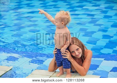 Little happy sports man stand at poolside - active baby swim with fun jump to mother hands in swimming pool. Family lifestyle and summer children water activity and swimming lesson with parents.