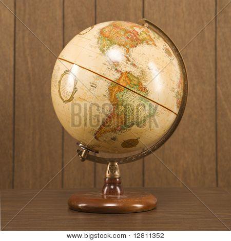 Sill life shot of a vintage world globe sitting on a desk.