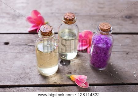 Organic cosmetics products. Sea salt bottles with oil and towels on vintage wooden background. Selective focus.