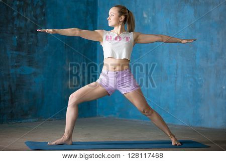Beautiful Sporty Young Woman Doing Warrior Ii Posture