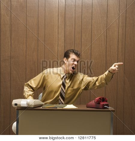 Caucasion mid-adult retro businessman sitting at desk pointing in anger.