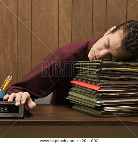 Caucasion mid-adult retro businessman sitting at desk with head down sleeping on a tall stack of folders.