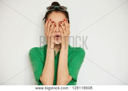 Isolated Headshot Of Funny Girl In Casual Shirt Covering Her Face With Both Hands. Young Female Mode