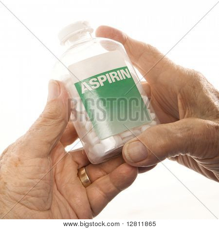 Close-up of elderly male Caucasion hands holding aspirin bottle.