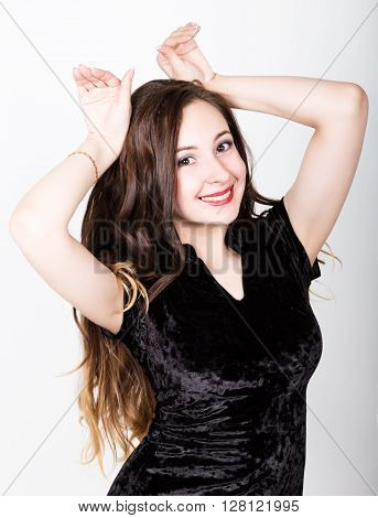Portrait of a funny casual woman showing rabbit geture over his head. different happy emotions..