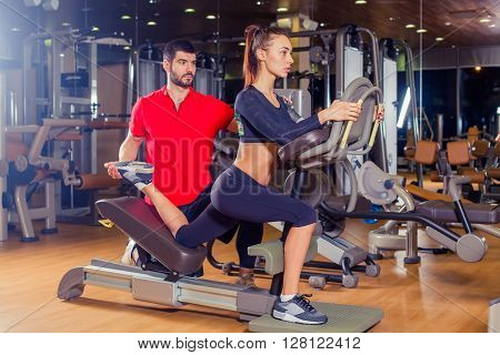 Personal trainer helping woman working with lunges, leg coaching.