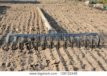 Rake on brown, grooved, loosened soil closeup